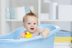 Adorable baby having bath in blue tub. Funny baby having bath in blue tub royalty free stock photo