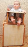 Adorable baby on highchair, at home Stock Image