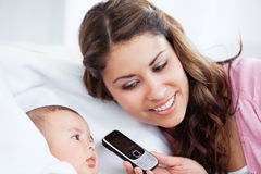Adorable baby with his mother holding a cellphone Royalty Free Stock Image