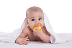 Adorable baby holding and bites yellow duck after shower Royalty Free Stock Photo