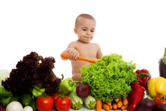 Adorable baby holding carrot and playing with vegetables Stock Images