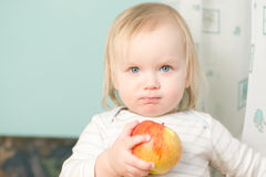 Adorable baby holding red orange apple Royalty Free Stock Photos