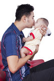 Adorable baby kissed by his dad Stock Image