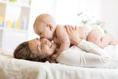 Adorable baby kissing his mother. Young women and little child have a fun pastime Royalty Free Stock Image