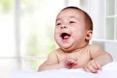 Adorable baby laughing on bed Royalty Free Stock Images