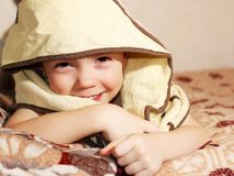 Adorable baby, looking out under yellow a towel royalty free stock images