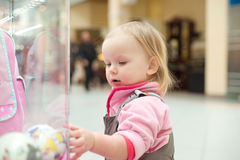 Adorable baby looking to baby toys in shop window Stock Photos