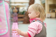 Adorable baby looking to toys in shop window Stock Images