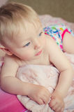 Adorable baby lying on the bed. Adorable naked baby boy with big blue eyes lying on the bed. Cute toddler in pink diaper lying on his stomach on the pink sheet Royalty Free Stock Photo