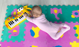 Adorable Baby lying on child friendly floor puzzle. Adorable baby lying on the floor Suitable for children puzzle carpet and playing the keyboard Royalty Free Stock Photography