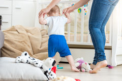 Adorable baby making first steps with mother at living room Stock Images