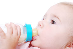 Adorable baby with milk bottle. Cute baby is drinking a milk from the bottle Stock Photo