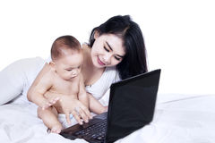 Adorable baby with mom working on a laptop Royalty Free Stock Photo