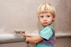 Adorable baby painting the wall with a brush. royalty free stock images