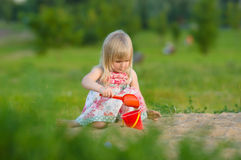 Adorable baby play with shovel and pail in sand Royalty Free Stock Photos