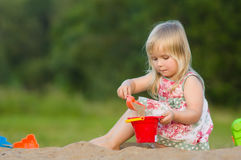 Adorable baby play with shovel and pail in sand Royalty Free Stock Photography