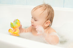 Adorable baby play with toy sit in bath Stock Images