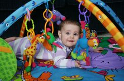Adorable baby playing. Cute baby lying on a jungle play activity mat surrounded by toys Royalty Free Stock Image
