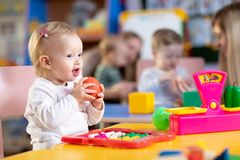 Adorable baby playing with educational toys with group of nursery kids under teacher supervision stock image