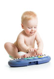 Adorable baby playing electronic piano Royalty Free Stock Image