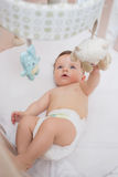 Adorable baby playing with toys in crib Royalty Free Stock Photography