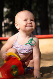Adorable baby plays in a sandbox. Blond white baby hold his bucket playing in a sandbox Royalty Free Stock Photography