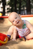 Adorable baby plays in a sandbox. Blond white baby smiles playing in a sandbox Royalty Free Stock Images