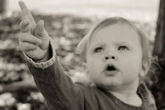 Adorable baby pointing up. Ward while looking deep in thought Stock Photo