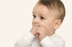 Adorable baby portrait with the hand in the mouth. Stock Image