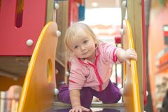 Adorable baby prepare to slide down on playground Stock Image