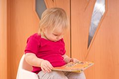 Adorable baby read small baby book Stock Photography