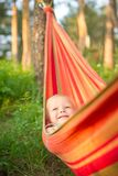 Adorable baby rest in hammock under trees Stock Images
