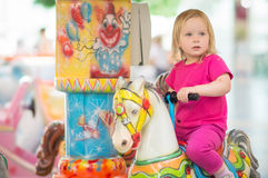 Adorable baby ride on carousel in mall Stock Photography