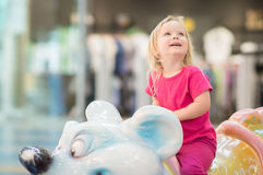 Adorable baby ride on carousel in mall Stock Photos