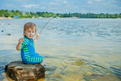 Adorable baby on river with fishing-rod Stock Images