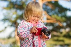 Adorable Baby Shoot Compact Camera In Park Stock Photos