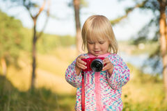 Adorable baby shoot compact camera in park Royalty Free Stock Photo