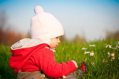 Adorable baby sit on hill and touch flowers Stock Images
