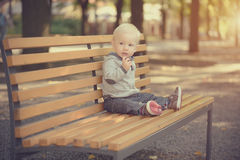 Adorable baby sitting on the bench Stock Photography
