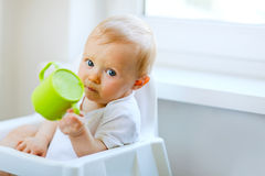 Adorable baby sitting in chair and holding cup Royalty Free Stock Photo