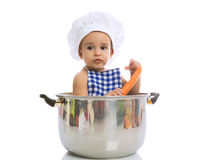 Adorable baby sitting in a chef's pot and holding fresh carrot. Isolated Royalty Free Stock Image