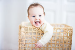Adorable baby sitting in a laundry basket. Adorable laughing baby sitting in a laundry basket Royalty Free Stock Photography