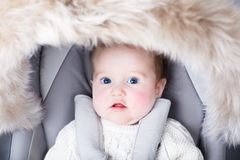 Adorable baby sitting in a warm stroller Stock Photography