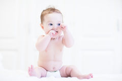Adorable baby sitting in a white nursery Stock Photo