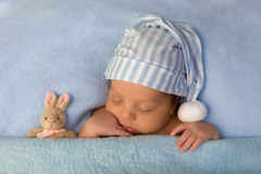 Adorable baby sleeping in blue bed royalty free stock photo