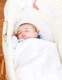 Adorable baby sleeping in his cradle Stock Images