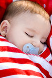 Adorable baby sleeping wrapped in a red blanket Royalty Free Stock Photography