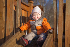 Adorable baby sliding from baby slide in park Stock Photos
