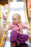 Adorable baby sliding down baby slide Stock Photography