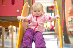 Adorable baby sliding down on playground Stock Photos